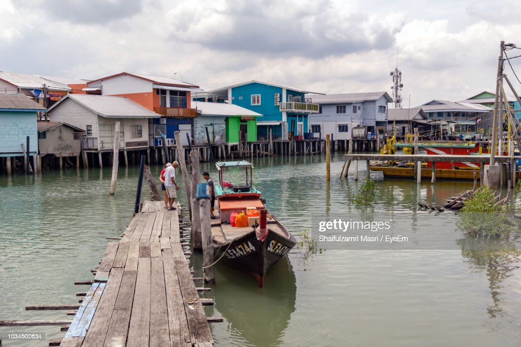 Boats Moored In Canal By Houses Against Sky : Stock Photo