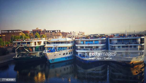 Boats Moored In City Against Clear Sky