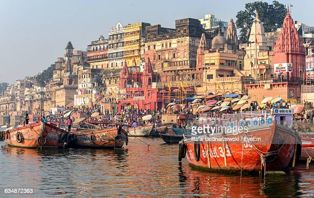 Boats Moored In Ganges River By Old Buildings Against Sky