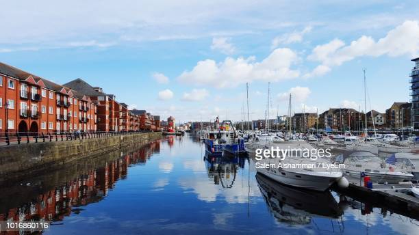 boats moored in harbor against buildings in city - swansea stock pictures, royalty-free photos & images