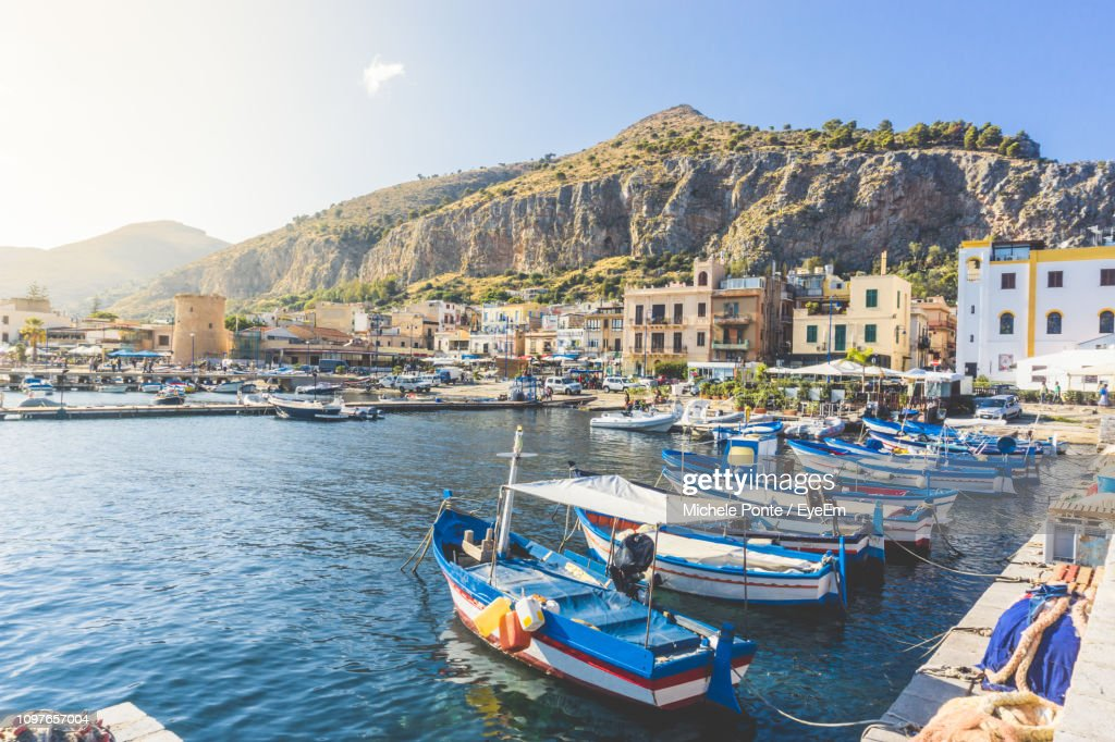 Boats Moored In Harbor Against Buildings In City : Stock Photo