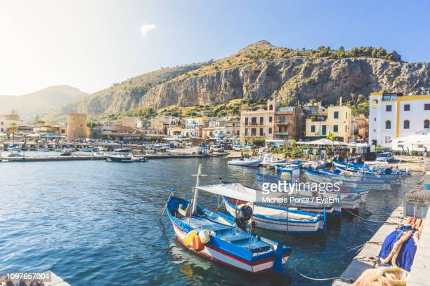 boats moored in harbor against buildings in city - sicilia foto e immagini stock