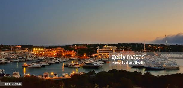 boats moored in harbor against clear sky - costa smeralda stock pictures, royalty-free photos & images