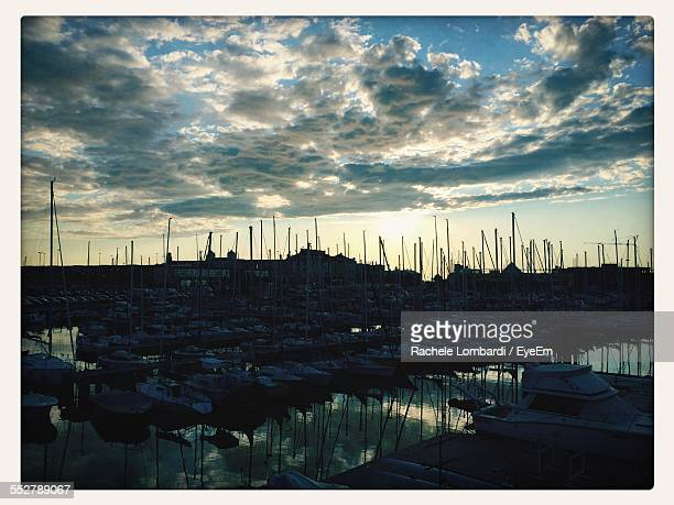 Boats Moored In Harbor Against Cloudy Sky