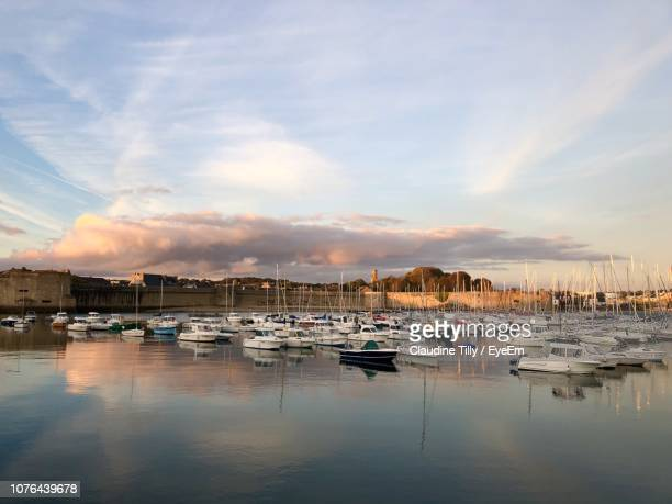 boats moored in harbor at sunset - concarneau stock-fotos und bilder