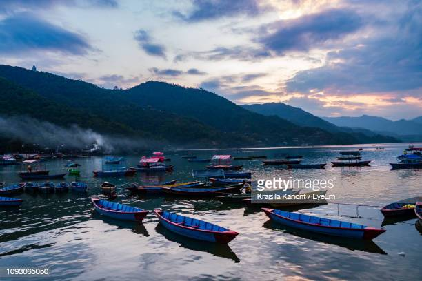 boats moored in lake against mountain range - kathmandu stock pictures, royalty-free photos & images