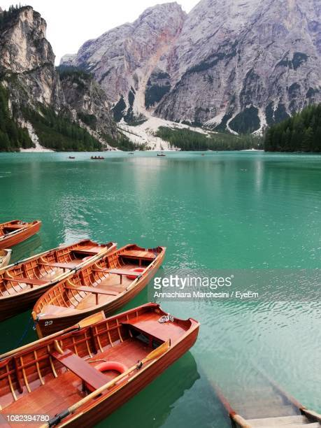 boats moored in lake against mountains - pragser wildsee stock pictures, royalty-free photos & images
