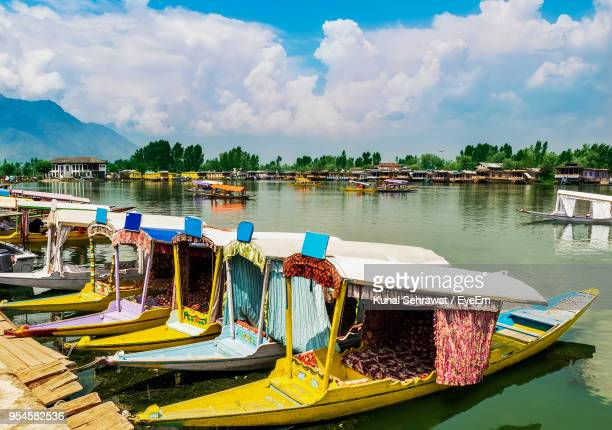 boats moored in lake against sky - kashmir stock photos and pictures