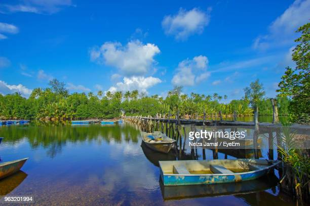 boats moored in lake against sky - terengganu stock pictures, royalty-free photos & images