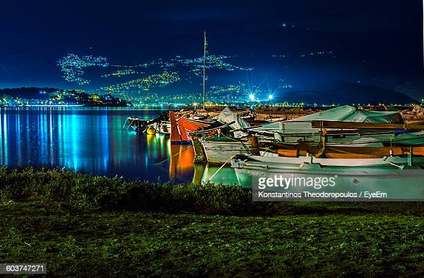 boats moored in lake at night - volos stock pictures, royalty-free photos & images