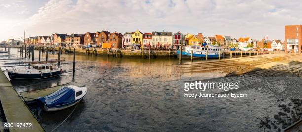 boats moored in river against buildings at harbor - husum stock-fotos und bilder