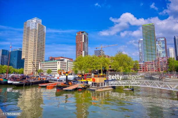 boats moored in river against buildings in city - hollande méridionale photos et images de collection