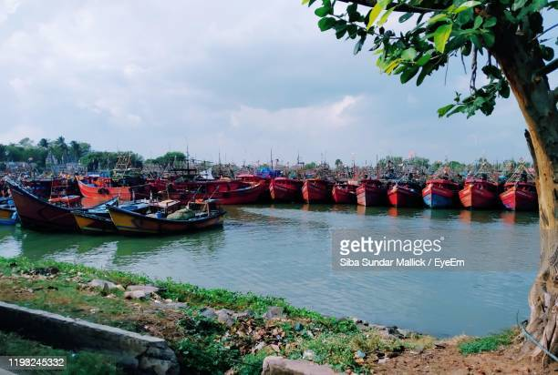 boats moored in river against sky - siba stock pictures, royalty-free photos & images