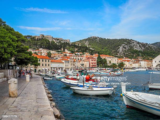 boats moored in river against town - hvar stock photos and pictures