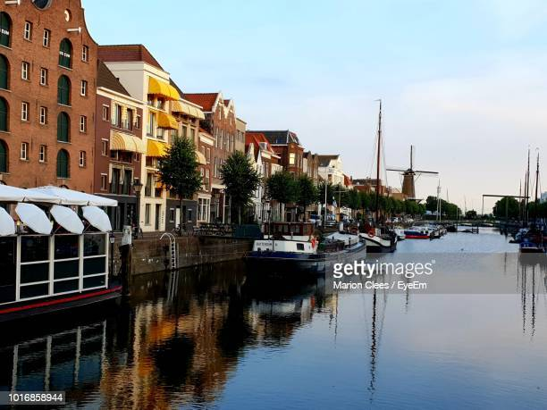boats moored in river by buildings against sky - rotterdam stock-fotos und bilder