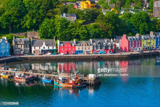 boats moored in river by buildings in city - harbour stock pictures, royalty-free photos & images