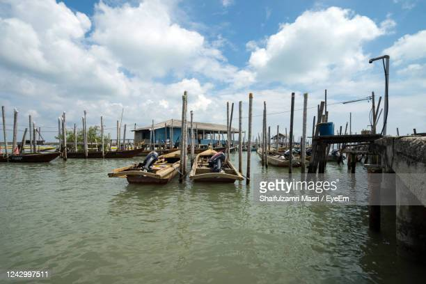 boats moored in river - shaifulzamri stock pictures, royalty-free photos & images