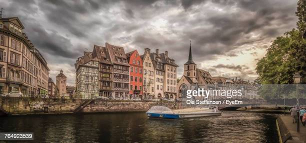 boats moored in river with buildings in background - strasbourg stock pictures, royalty-free photos & images