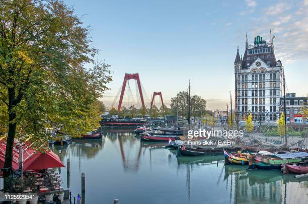 boats moored in river with city in background - rotterdam stock pictures, royalty-free photos & images