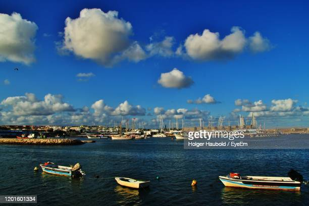 boats moored in sea against blue sky - faro district portugal stock pictures, royalty-free photos & images