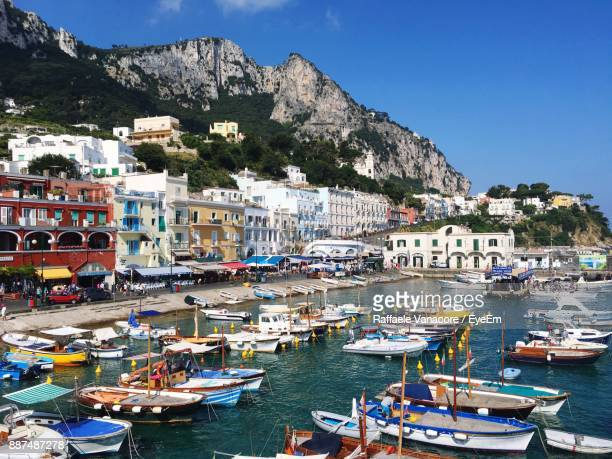 boats moored in sea against blue sky - capri stock pictures, royalty-free photos & images