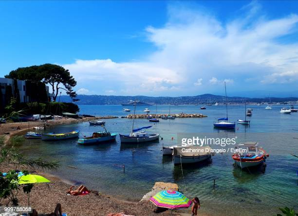 boats moored in sea against blue sky - antibes stock photos and pictures