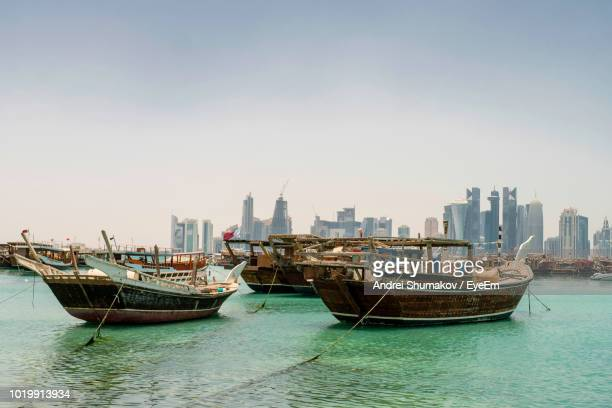 boats moored in sea against buildings in city - doha stockfoto's en -beelden