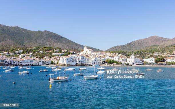 Boats Moored In Sea Against Clear Blue Sky