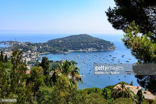 boats moored in sea against clear sky - saint jean cap ferrat stock pictures, royalty-free photos & images