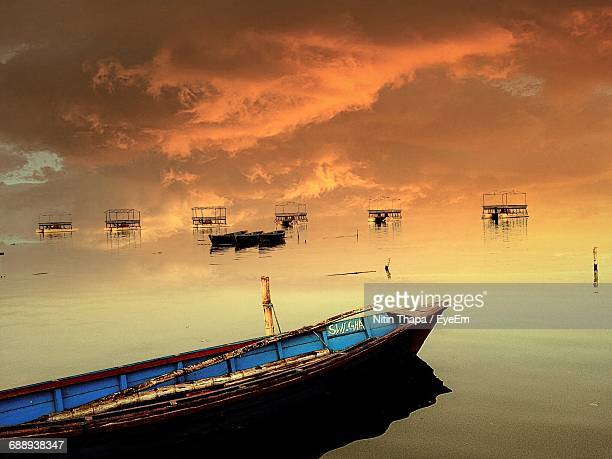 Boats Moored In Sea Against Cloudy Sky During Sunset