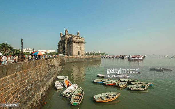 Boats Moored In Sea Against Gateway To India And Clear Sky