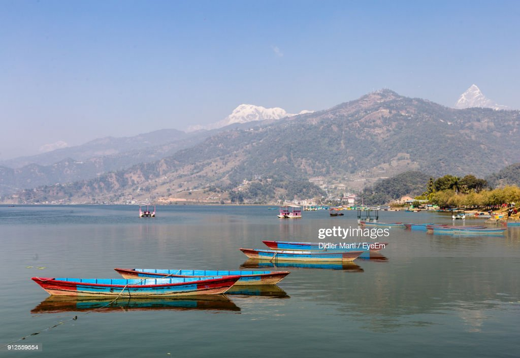 Boats Moored In Sea Against Mountains : Stock Photo