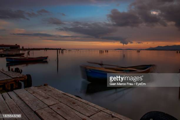boats moored in sea against sky during sunset - frau photos et images de collection