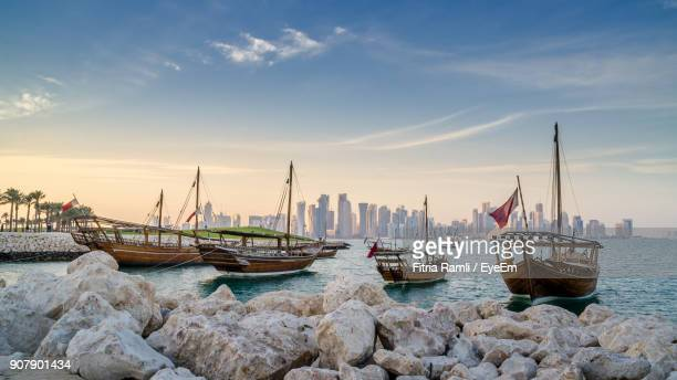 boats moored in sea against sky during sunset - doha stockfoto's en -beelden