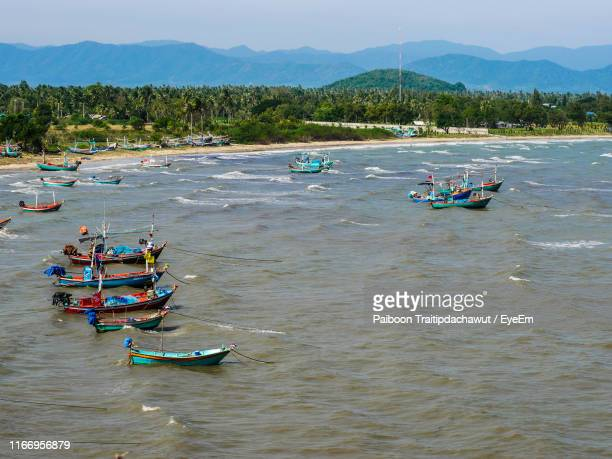 boats moored in sea against sky - prachuap khiri khan province stock pictures, royalty-free photos & images