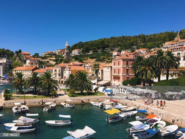 boats moored in sea at harbor by town against clear blue sky - hvar stock photos and pictures
