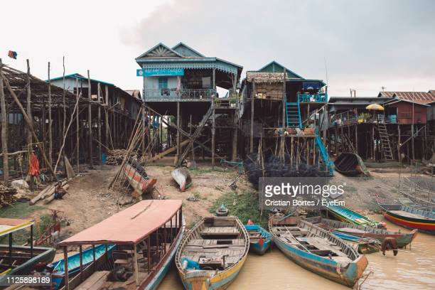 boats moored in sea by stilt houses against sky - bortes stockfoto's en -beelden