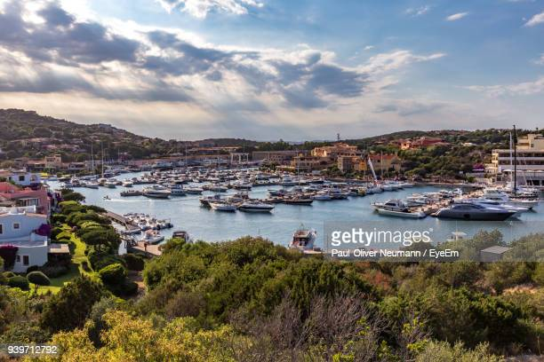 boats moored in sea by town against sky - costa smeralda stock pictures, royalty-free photos & images