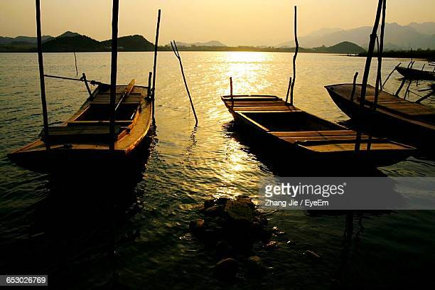 Boats Moored In Sea During Sunset