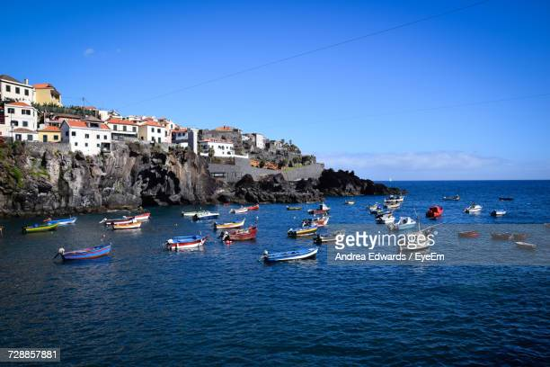 boats moored in sea - madeira island stock photos and pictures