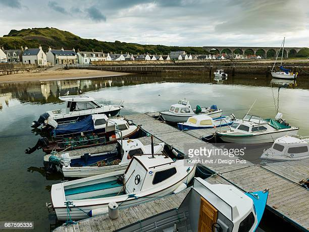 boats moored in the tranquil harbour of the north sea with houses in the background - モーレイ湾 ストックフォトと画像