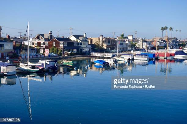 boats moored in water against clear blue sky - newport beach stock pictures, royalty-free photos & images