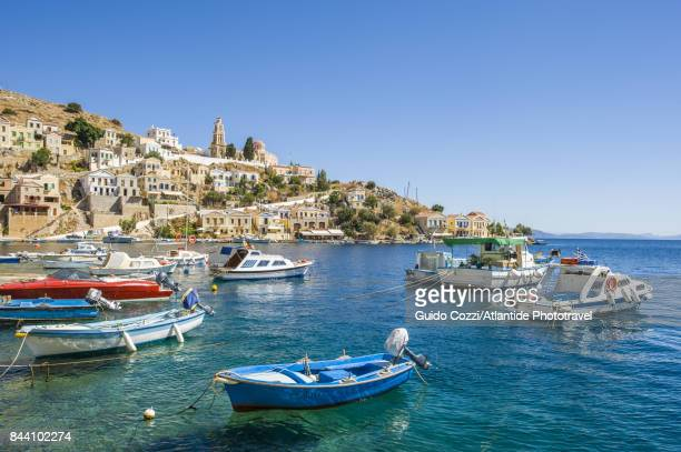 boats moored near the village - symi stock photos and pictures