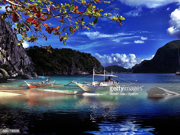 Boats Moored On Beach By Mountains