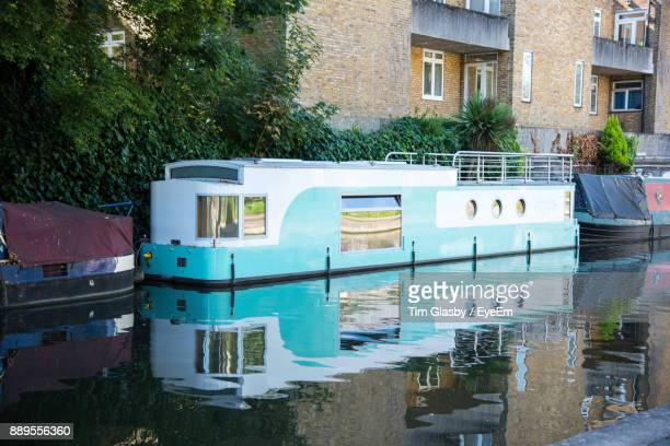 boats moored on canal against building - houseboat stock pictures, royalty-free photos & images