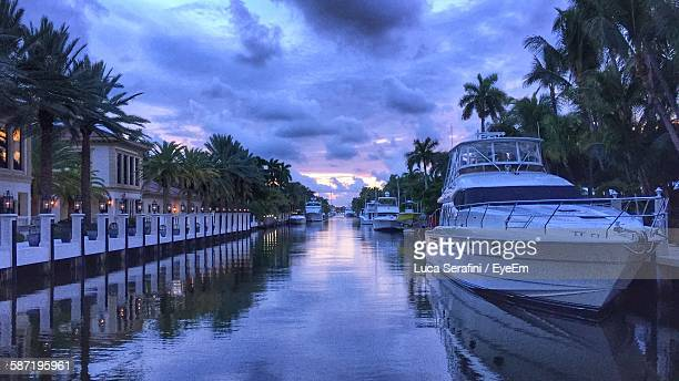 Boats Moored On Canal Against Cloudy Sky