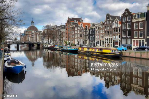 boats moored on canal amidst buildings in city - north holland stock pictures, royalty-free photos & images