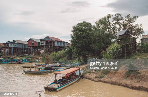 boats moored on canal by buildings against sky - bortes ストックフォトと画像