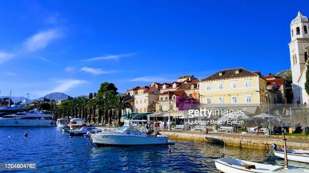 boats moored on canal by buildings in city against sky - ljubomir belic stock pictures, royalty-free photos & images