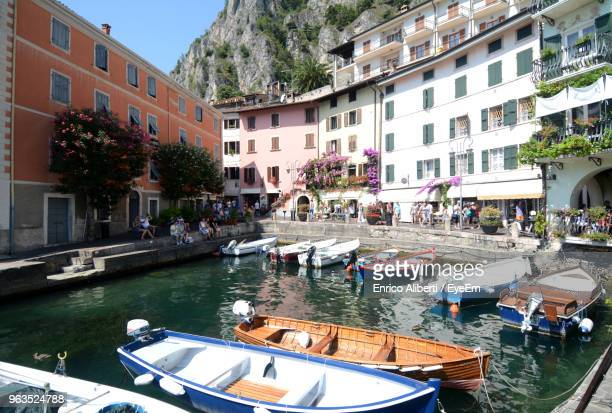 boats moored on canal by buildings in city - enrico aliberti stock-fotos und bilder